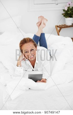 Senior Woman Lying In Bad And Reading A Tablet