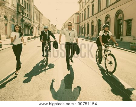 Business people riding on bikes and running in city - retro style photograph