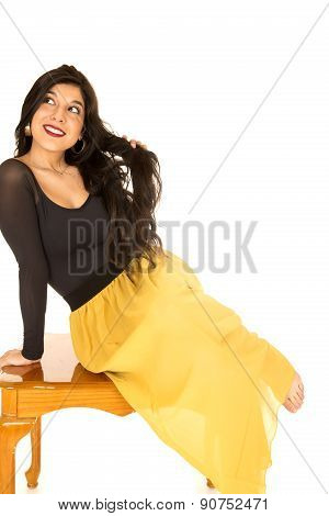 Gorgeous Female Sitting On A Coffee Table Playing With Her Hair