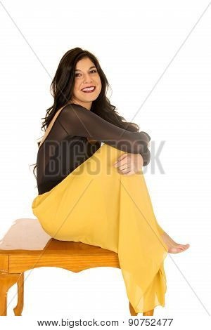 Beautiful Brunette Woman Sitting On A Coffee Table Smiling
