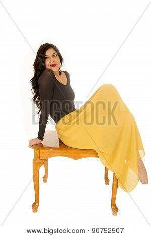 Female Model Wearing A Black Top And Yelllow Skirt Sitting On Coffee Table