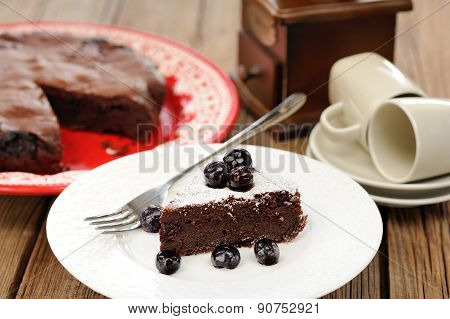 Piece Of Chocolate Pie With Whole Blueberries And Icing Sugar In White Plate With Pie And Coffee Cup