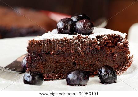 Piece Of Chocolate Pie With Blueberry And Icing Sugar In White Plate