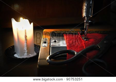 Old Sewing Machine, Fabric And Rusty Scissors At The Light Candle. Close Up, Low Key