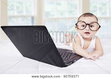 Attractive Male Baby With Laptop On Bed