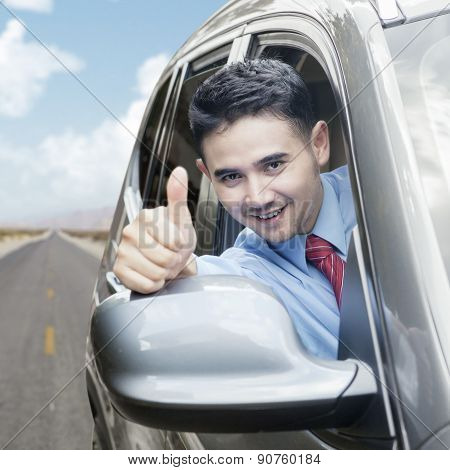 Happy Businessman Showing Thumb Up In Car