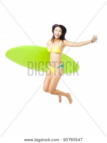 Happy Young Woman  Holding Surfboard And Jumping