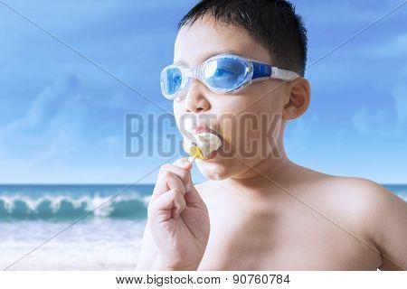 Male Kid Bites Ice Cream At Seaside