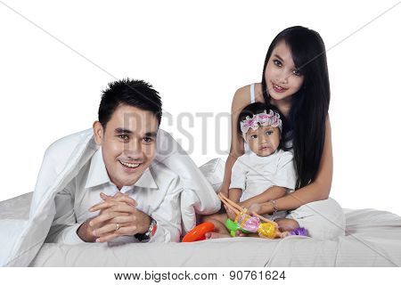 Portrait Of Joyful Family On Bed