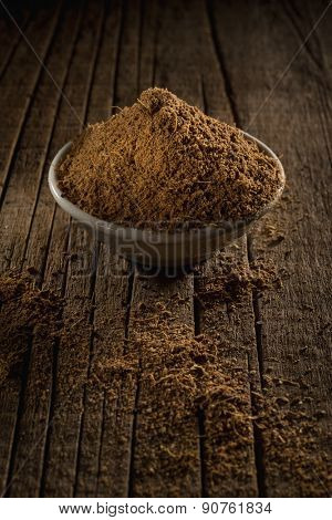 Black tea with spices for Garam Masala Chai Tea against wooden background