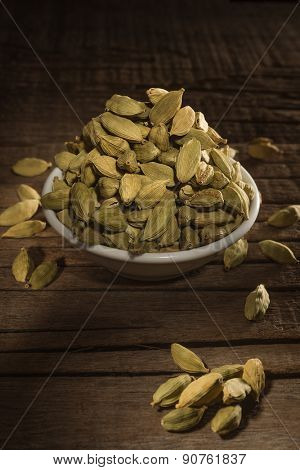 Green cardamom seeds against wooden background