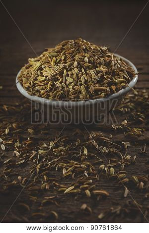 Fennel seeds in a small bowl on an old wooden table.
