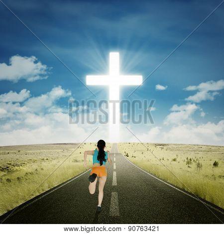 Woman Running Toward A Cross
