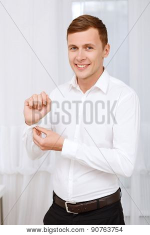 Smiling man buttoning up sleeve