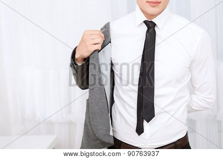 Close up of man putting on jacket.