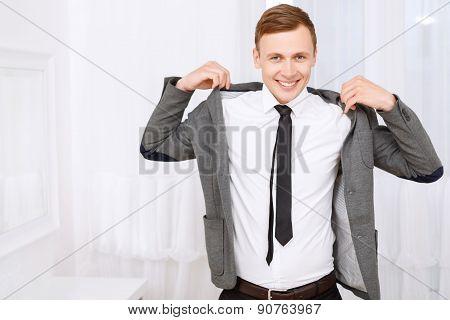 Smiling man putting on jacket