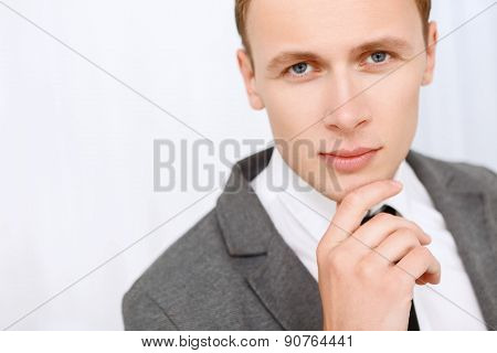 Close up of man touching his chin.