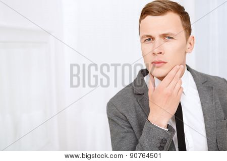 Young man checking his bristle hair on face
