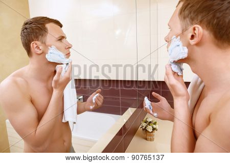 Topless man applying shaving cream on face