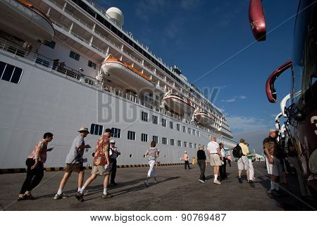 Unidentified tourists walking besides luxury cruise in the port of Manta, Ecuador
