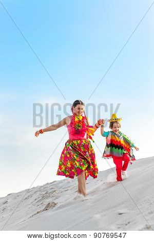 Cheerful boy and his happy mother running on sand