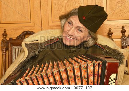 elderly woman solder playing accordion closeup