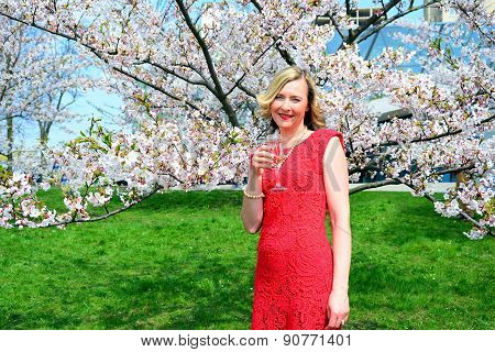 Beautiful Female With Glass Of Champain In The Sakura Garden