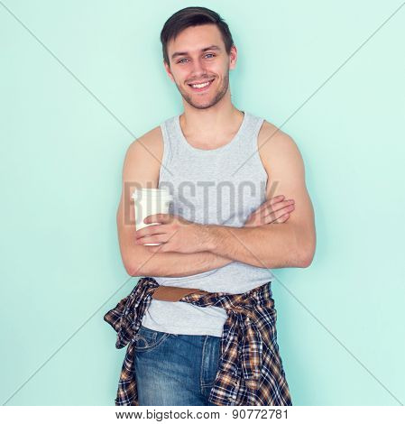 Portrait young man arms crossed holding paper cup of coffee city street casual urban style looking a