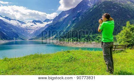 Young man photographingalpine lake, Austria