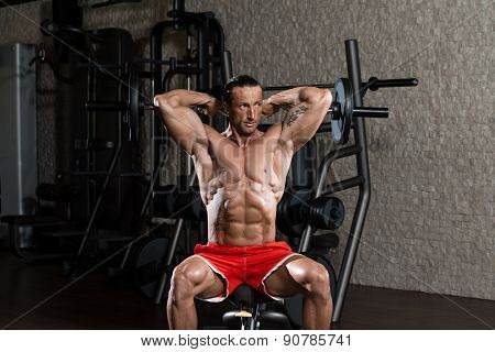 Bodybuilder Exercising Triceps With Barbell