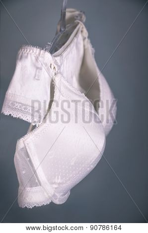 White Lace Lingerie Hanging On The Hanger On The Gray-blue Background. Vertical