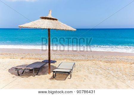 Reed beach umbrella with two loungers on beach at sea