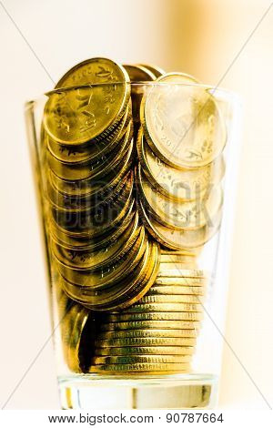 Wealth management ~ Currency or coins saved in a glass on a plain background.