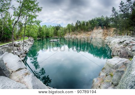 Cloudy Skies And Reflections At A Quarry