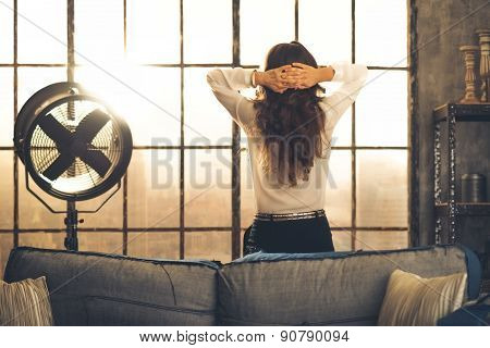 Woman Standing In A Loft With Hands Laced Behind Her Head