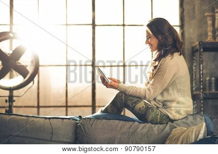 Smiling Woman Relaxing On Back Of Sofa Holding A Tablet Pc