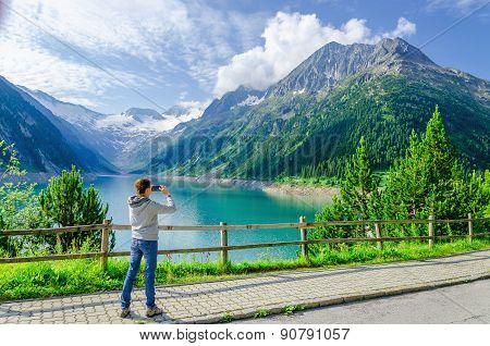 Young woman photographing alpine lake, Austria
