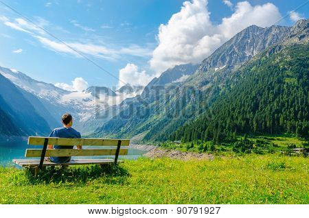 Young man sits on bench by azure mountain lake