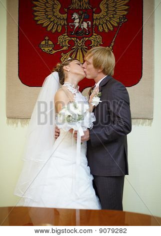 Newly Married Kiss Under Russian Arms