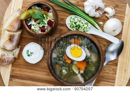 Sorrel soup in wooden bowl with egg and salad