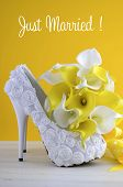 stock photo of calla  - Yellow and white theme floral wedding bridal high heel shoes with calla lilly bouquet on shabby chic white wood table and yellow background - JPG