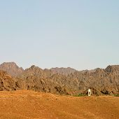 image of oman  - A minaret hidden in a valley in the Hajar Mountains near the town of Ray in the Sultanate of Oman - JPG