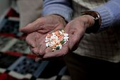 stock photo of home remedy  - Old woman is holding medications in her hands - JPG