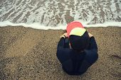 picture of single man  - Handsome young surfer man sitting at sand near ocean young beautiful surfer man in black diving suit sitting on the beach - JPG