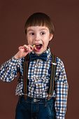 picture of lollipop  - elegant fashionable boy eating lollipop isolated on brown background - JPG