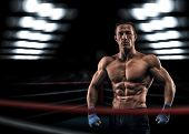 image of boxing ring  - A strong man in the ring in blue boxing bandages preparing for battle - JPG