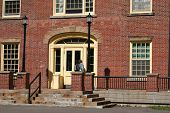 stock photo of school building  - student entering the front door of a university building - JPG