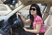 picture of steers  - Portrait of young woman steering a car while wearing sun glasses and smiling on the camera  - JPG