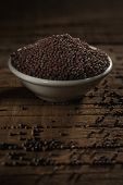 stock photo of mustard seeds  - Black mustard seeds against a wooden background  - JPG
