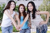 picture of joining hands  - Three happy female students standing at schoolyard while joining hands together - JPG